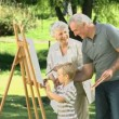 Boy painting a canvas with his grandparents — Stock Video