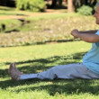 Vídeo Stock: Elderly male doing warm up sitting on grass