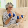 Old woman working her muscles with dumbbells — Stock Video #22706867