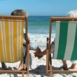 Aged couple looking at the ocean sitting on beach chairs — Stock Video