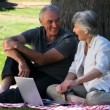 Old man and woman using a laptop sitting on a tablecloth — Vídeo de stock