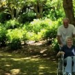 Man strolling with his wife in a wheelchair — Vídeo de stock