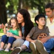 Family enjoying time together sitting on the grass — Stockvideo #22707609