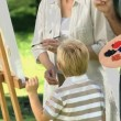 Stock Video: Boy and grandparents painting canvas