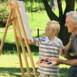 Stock Video: Young child painting canvas with grandfather