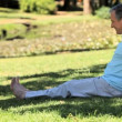 Old mdoing warm up sitting on grass — Vídeo de stock #22708221