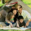 Family looking at a map siiting in front of a tent — Stock Video
