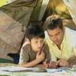 Stock Video: Father and son looking at a map lying in a tent