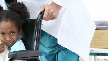 Ragazza carina seduta in una sedia a rotelle — Video Stock