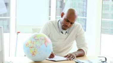 Ethnic businessman looking at a terrestrial globe — Stock Video