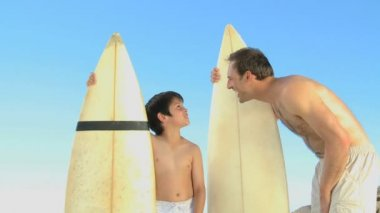 Father and son with surfboard talking with each other — Stock Video