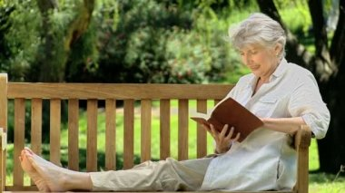 Elderly female reading a book sitting on a bench — Stock Video