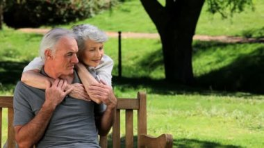 Senior woman hugging her man sitting on a bench — Stock Video