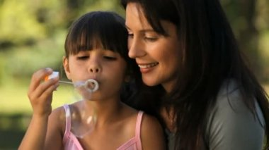 Mom and daughter blowing bubbles sitting on the grass — Stock Video