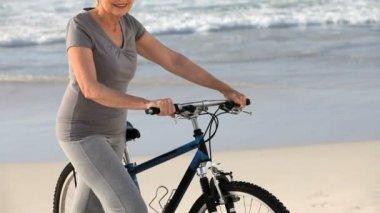 Femme âgée en regardant la caméra avec un vélo — Vidéo