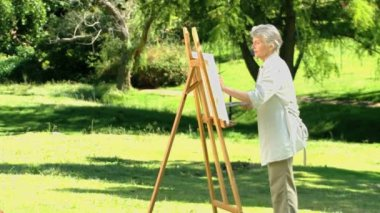 Old woman painting a canvas — Stock Video