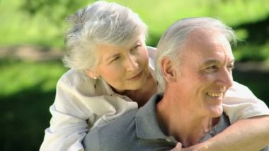 Close up of a old woman hugging her husband sitting on a bench — Stock Video