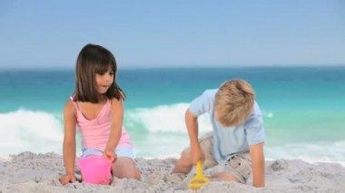 Cute children building a sand castle — Stock Video
