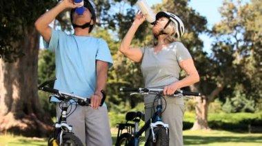 Elderly couple on bikes taking a break — Stock Video