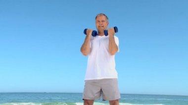 Leeftijd man aan het werk zijn spieren met halters — Stockvideo