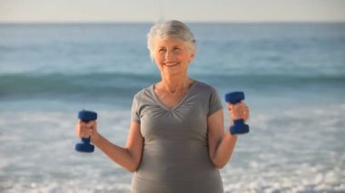 Aged woman working his muscles with dumbbells — Stock Video