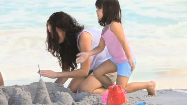 Beautiful mother building a sand castle with her daughter — Stock Video