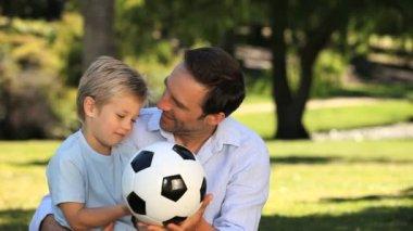 папа и сын играл с футбольным мячом, сидя на траве — Стоковое видео