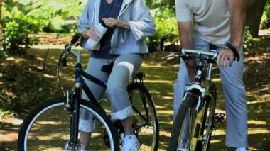 Elderly couple drinking and biking — Stockvideo