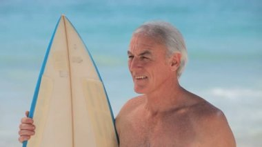 Closeup of a senior man looking at the ocean with a surfboard — Stock Video