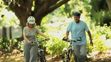 Senior couple walking and pushing bikes — Stock Video