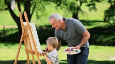 Young boy painting a white canvas with grandad — Stock Video