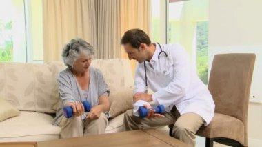 Joven médico mostrando a una mujer el uso de mancuernas — Vídeo de stock