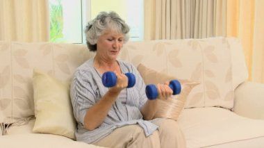 Old woman working her muscles with dumbbells — Stock Video