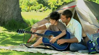 Father teaching guitar to his son in front of a tent — Stock Video