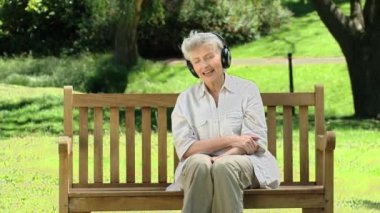 Elderly woman listening to musicon a bench — Stock Video