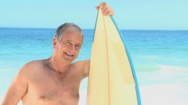 Elderly man posing with a surfboard — Stock Video