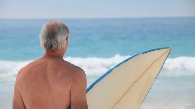 Starší muž pohledu na oceán s surfovací prkno — Stock video