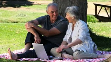 Old man and woman using a laptop sitting on a tablecloth — Stock Video