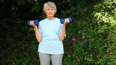 Oude vrouw die werkt haar spieren met halters — Stockvideo