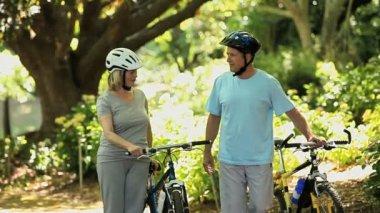 Elderly couple walking and pushing bikes — Stock Video