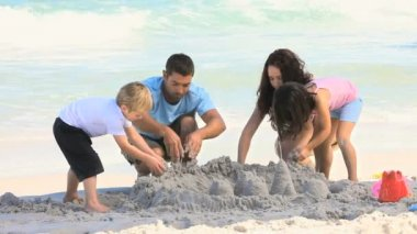 Parents building a sand castle with their children — Stock Video