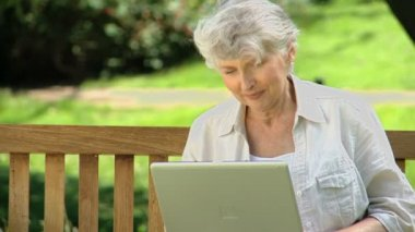 Senior woman looking at a laptop sitting on a bench — Stock Video