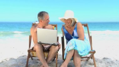 Elderly man showing to his wife a video on the laptop — Stock Video