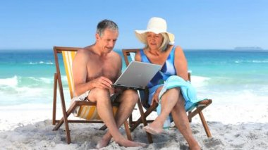 Elderly couple using a laptop sitting on beach chairs — Stock Video