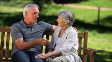 Senior couple laughing on a bench — Stock Video