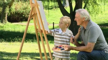 Young child painting a canvas with grandfather — Stock Video
