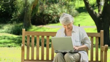 Old woman looking at a laptop sitting on a bench — Stock Video