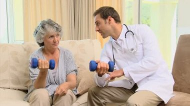 Doctor showing to his patient the use of dumbbells — Stock Video