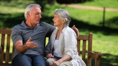 Senior couple talking on a bench — Stok video