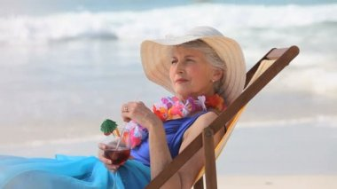 Elderly woman looking at the horizon with a cocktail sitting on a beach chair — Stock Video